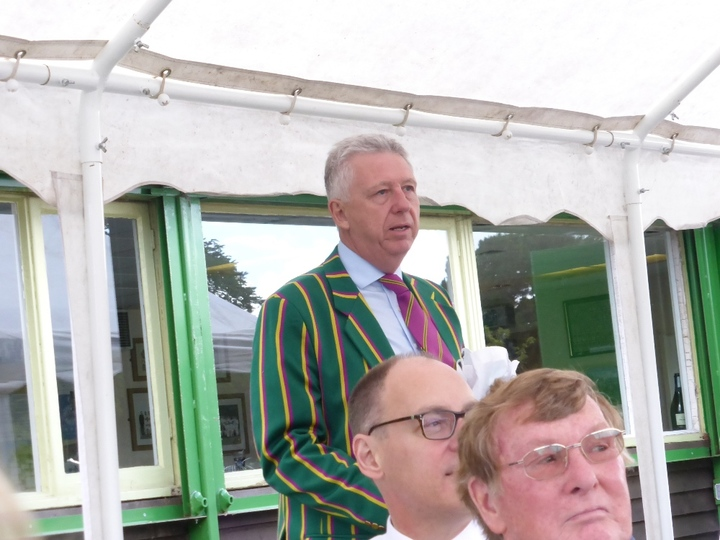 Chairman David Barrs distracted from his speech by the match