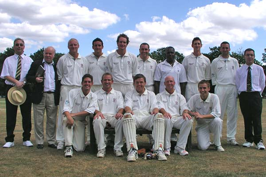 "Back row: Adams (Umpire); Stuart (Scorer); Sains; Ayres; Walford; Webb; Walker (""Patrick Truman""); Degg; Belchamber; Old England umpire.  Front row:  Fryd; Cocklin; Boon; Sutherland, Childs"