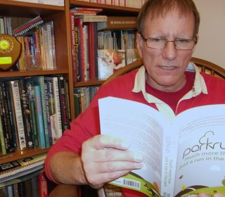 John Richardson reading the parkrun book, 'much more than just a run in the park.'