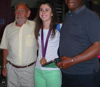 Olivia Breen proudly displaying her Paralympic bronze medal alongside club sprint coaches Bungey Williams and Leroy Elliott. awards